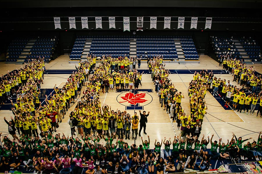 "A large group of new students and orientation leaders form the word ""NEW"" with their bodies during New Roots 2019/2020."