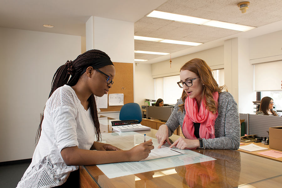 Academic advisor working with a student at the help desk within the Registrar's office.