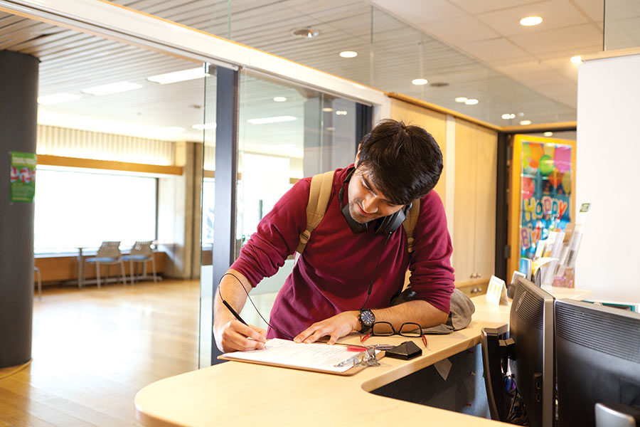 Student at the front desk of the Office of Residence and Student Life applying for a music pass.